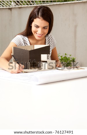 A young female architect working on a model and blueprints - stock photo