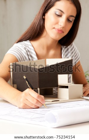 A young female architect working on blueprints with a model house - stock photo