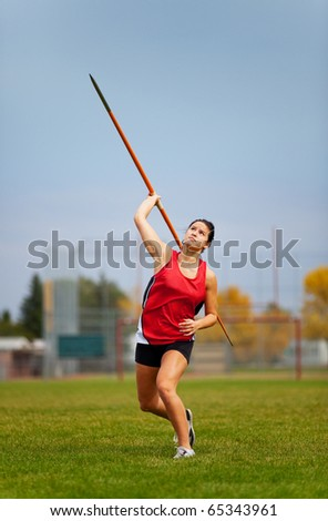 A young, female athlete throwing a javelin in a track and field event. - stock photo
