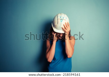 A young female builder wearing a hard hat is talking on the phone