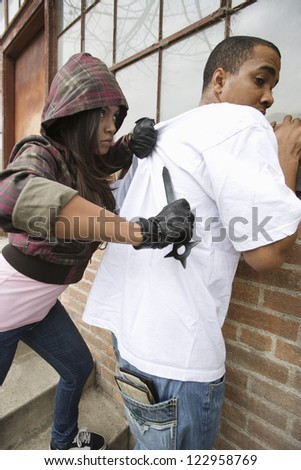 A young female criminal scaring young man with a knife on his back