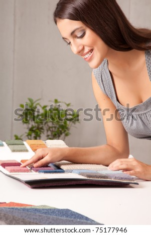 A young female designer choosing a carpet sample from a catalogue - stock photo