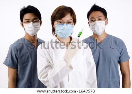 A young female doctor holds a green syringe partnered by two male doctors