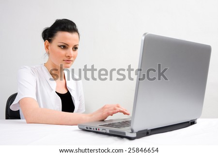 A young female doctor, working/browsing on a laptop - part of a series. - stock photo