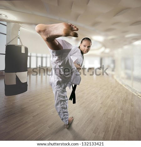 A young female dressed in kimono clothes performing a martial arts high kick in gym - stock photo