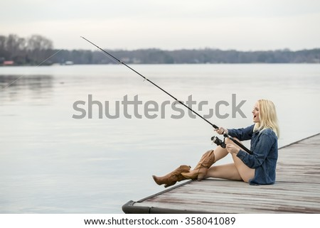 A young female fishes off a boat dock