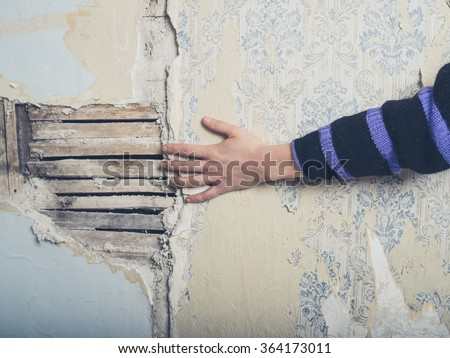 A young female hand is touching an old exposed lath wall