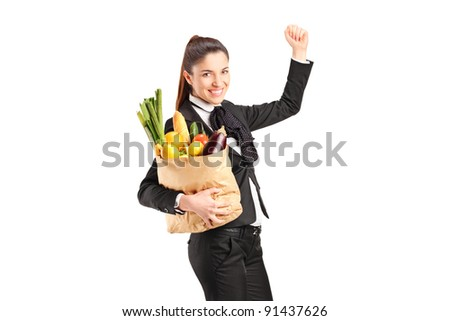 A young female holding a paper bag full of groceries isolated on white background - stock photo