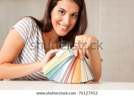 A young female interior designer displaying a group of color swatches.  Sharp focus on swatches - stock photo