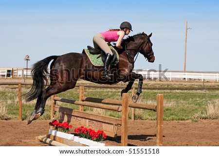A young, female jockey on her horse leaping over a hurdle. - stock photo