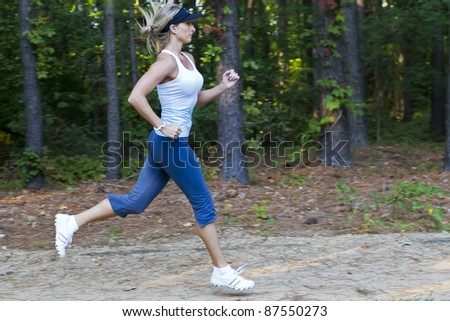 A young female jogger running through the woods - stock photo