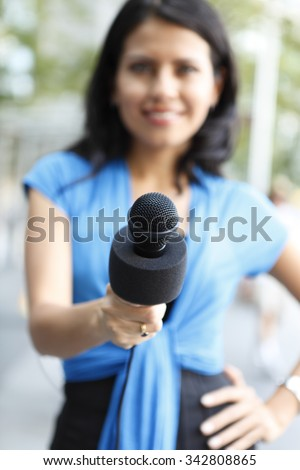 A young female journalist is holding her microphone towards viewer. The focus is on the microphone. - stock photo
