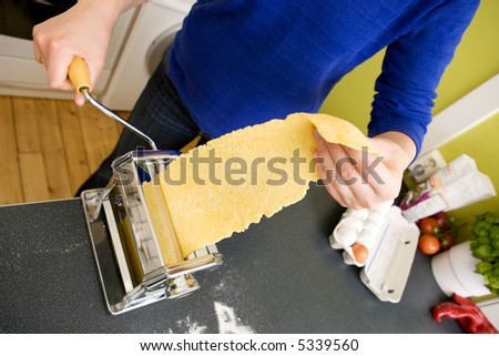A young female makes pasta at home in the kicthen - stock photo