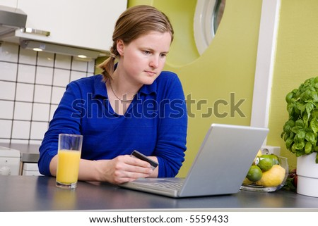 A young female making an online purchase from her kitchen. - stock photo