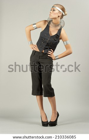 A young female model posing on a gray background wearing futuristic elements on her.