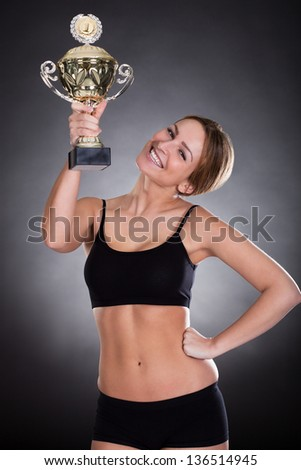 A Young Female Player Raising Her Trophy