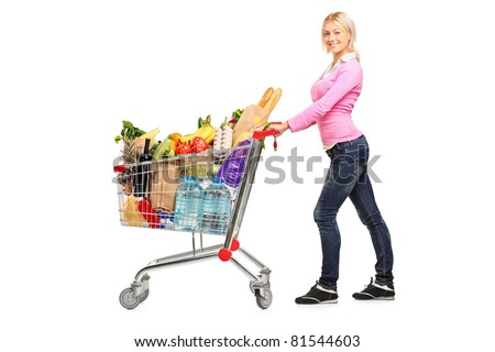 A young female pushing a shopping cart full with groceries isolated on white background - stock photo