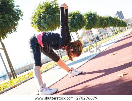 A young female runner stretching her muscles before jogging. - stock photo