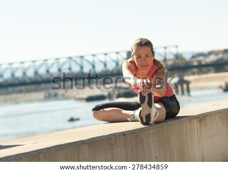 A young female runner stretching her muscles before jogging - stock photo