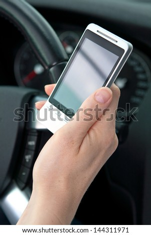 A young female's hand holding a smartphone while driving. Closeup image, focus on the phone. - stock photo
