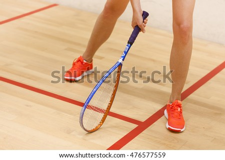 A young female squash player in a squash court