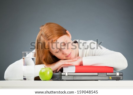 A young female student sleeping over a textbook and a notebook computer instead of studying. - stock photo