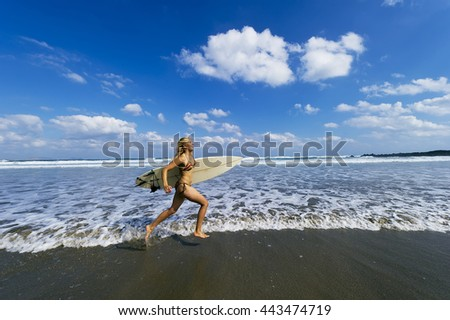 A young female surfer running along the Ocean break.