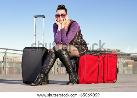 A young female traveler looking fed up and bored with her baggage in an airport terminal scenario - stock photo