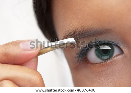 A young female using eyebrow tweezers PS:shallow depth of field