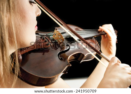 A young female violinist holding a violin or fiddle on a black background - stock photo