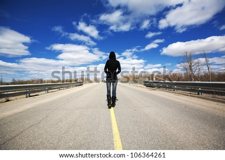 A young female walking down the middle of the road maybe lost in thought or not knowing where life will take her. - stock photo