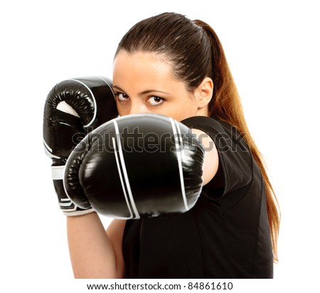 A young female wearing black boxing gloves on an isolated white background