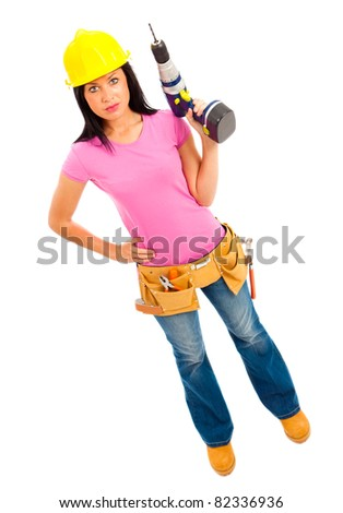 a young female wearing pink top blue jeans and tool belt holding an electric drill on isolated white background - stock photo