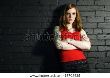 A young female with full arm tattoo leaning up against a black brick wall. - stock photo