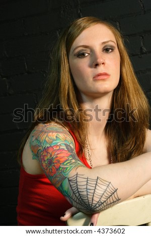 A young female with serious stare and arm tattoo. - stock photo