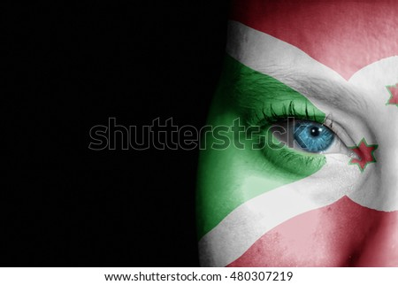 A young female with the flag of Burundi painted on her face on her way to a sporting event to show her support.