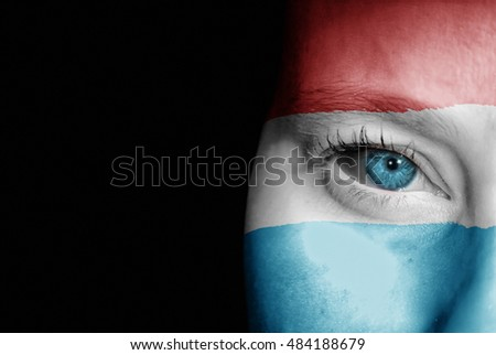 A young female with the flag of Luxembourg painted on her face on her way to a sporting event to show her support.
