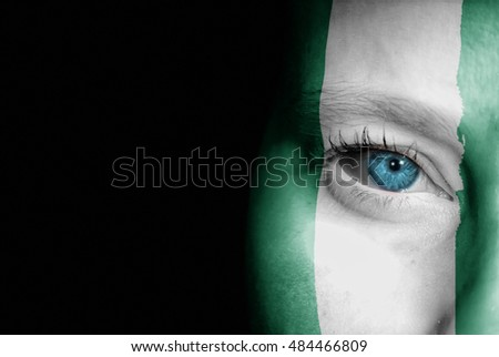 A young female with the flag of Nigeria painted on her face on her way to a sporting event to show her support.