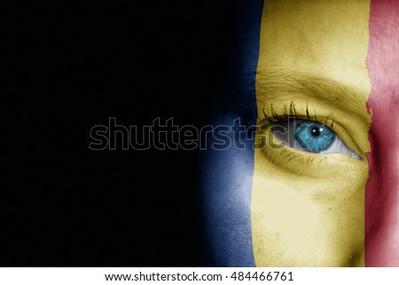 A young female with the flag of Romania painted on her face on her way to a sporting event to show her support.