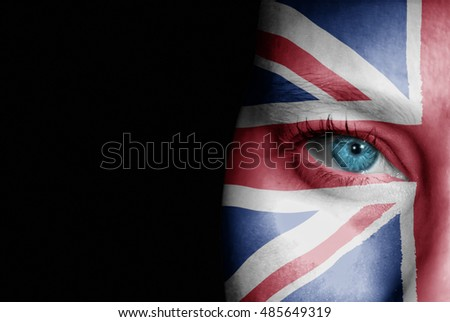 A young female with the flag of United Kingdom painted on her face on her way to a sporting event to show her support.