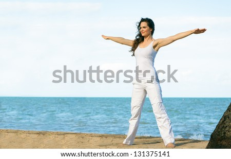 A young fit beautiful woman doing yoga on a beach with lots of copyspace. - stock photo