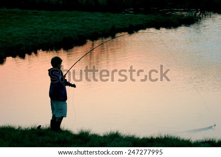 A young flyfisherman besides a lake at dusk. - stock photo