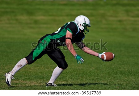 A young, football player about to catch the ball. - stock photo