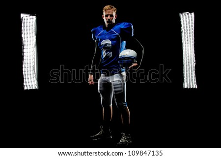 A young football player stands in front of the lights in his uniform holding his helmet. - stock photo