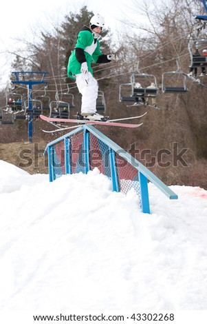 A young freestyle skier grinding down a rail on his skis. - stock photo