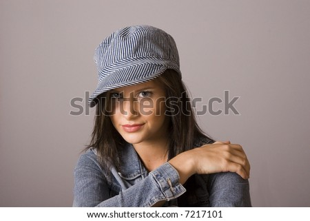 A young fresh fashion model posing with denim jacket and hat