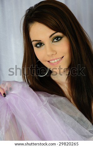 a young fresh female model smiling at the camera holding up lilac fabric