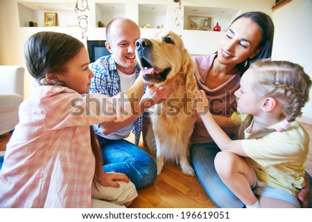 A young friendly family of four cuddling their pet - stock photo
