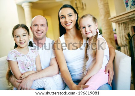 A young friendly family of four looking at camera - stock photo