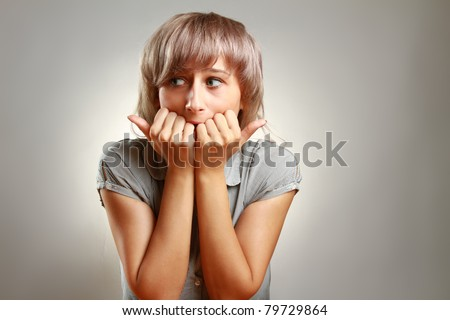 A young frightened woman, isolated on grey - stock photo